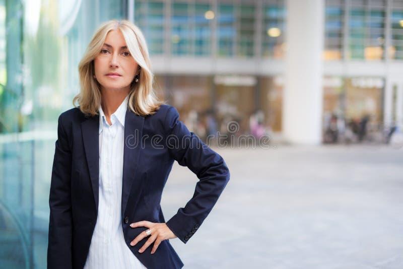 Mujer de negocios que se coloca al aire libre fotografía de archivo