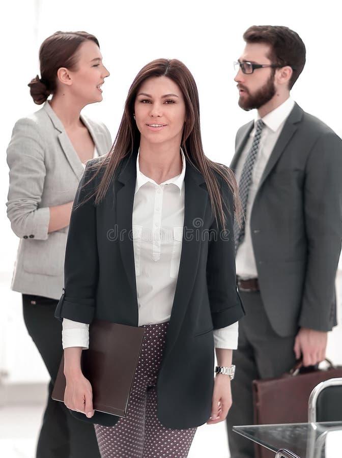 Mujer de negocios que se coloca cerca del escritorio imagenes de archivo