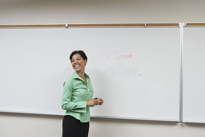 Mujer de negocios que se coloca en Front Of Whiteboard imagenes de archivo