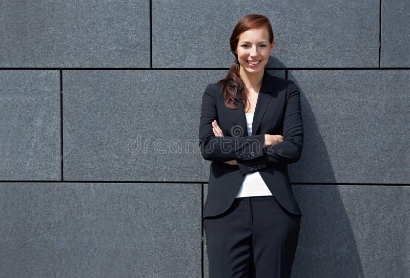 Mujer de negocios que se inclina en la pared imagen de archivo libre de regalías