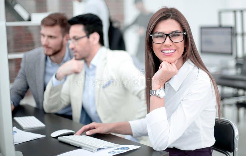 Mujer de negocios que se sienta en el escritorio de oficina fotos de archivo