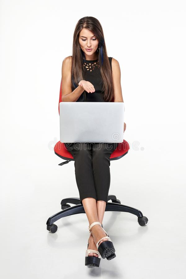 Mujer de negocios que se sienta en la silla de la oficina que trabaja con el ordenador portátil fotos de archivo