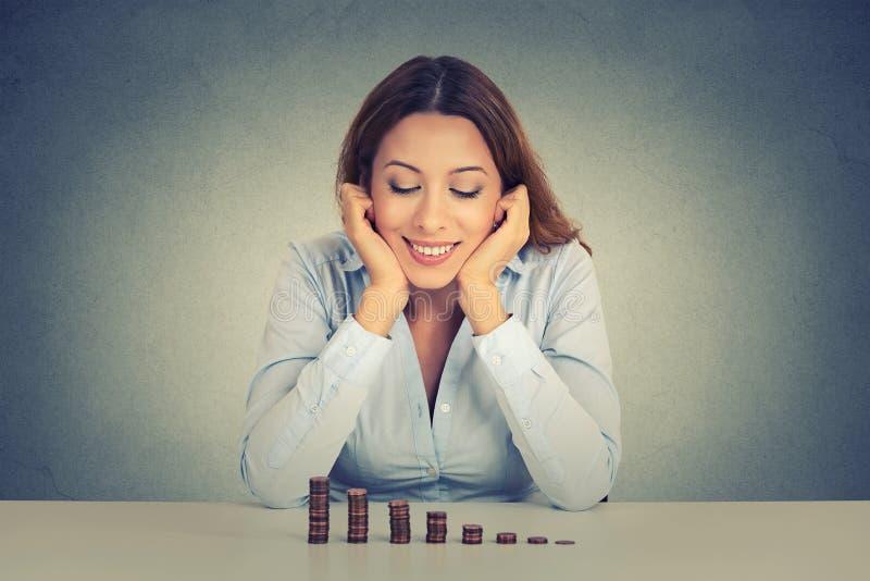 Mujer de negocios que se sienta en la tabla que mira la pila creciente de monedas imagenes de archivo