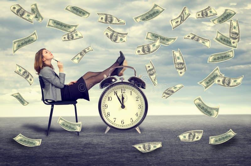 Mujer de negocios que se sienta en una silla debajo de una lluvia del dinero fotografía de archivo libre de regalías