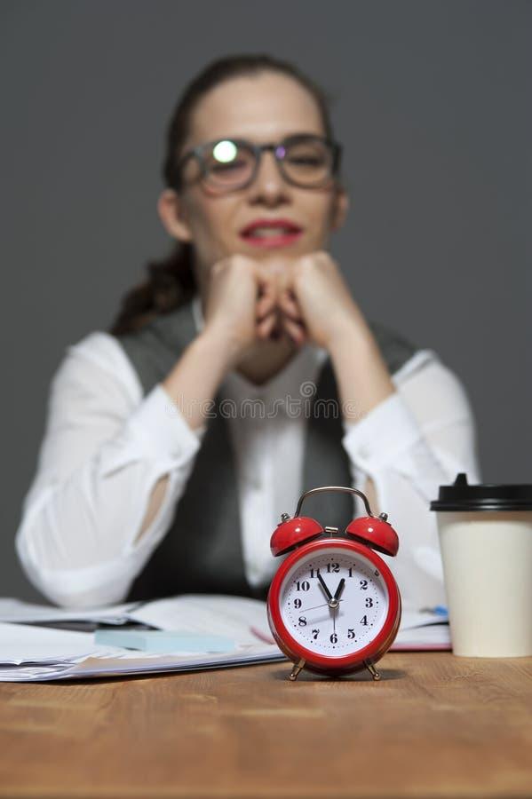 Mujer de negocios que se sienta para presentar con el despertador rojo imagen de archivo