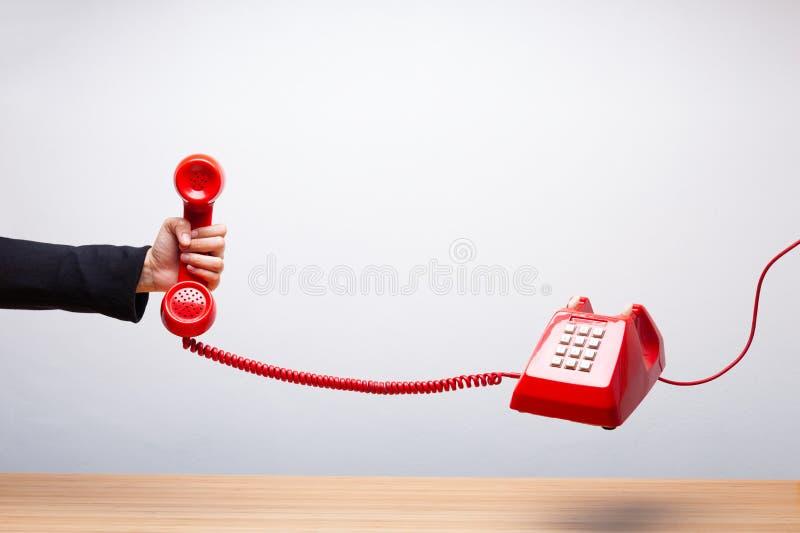 Mujer de negocios que sostiene el teléfono rojo foto de archivo