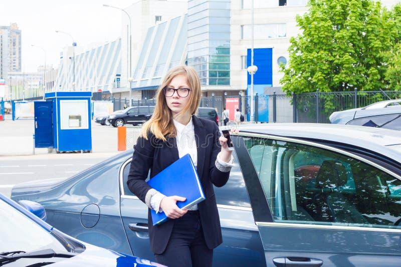 Mujer de negocios que sostiene la carpeta con los documentos dentro y fuera de su coche fotografía de archivo libre de regalías