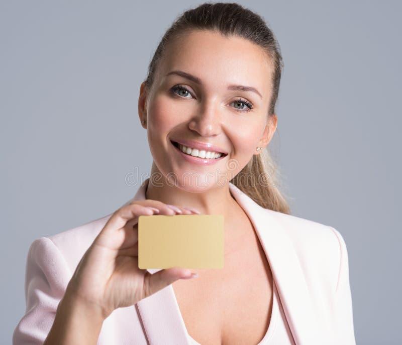 Mujer de negocios que sostiene la tarjeta de crédito contra su cara aislada fotos de archivo libres de regalías