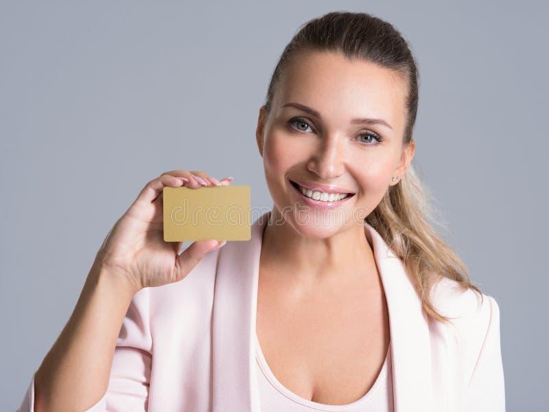 Mujer de negocios que sostiene la tarjeta de crédito contra su cara aislada imagen de archivo