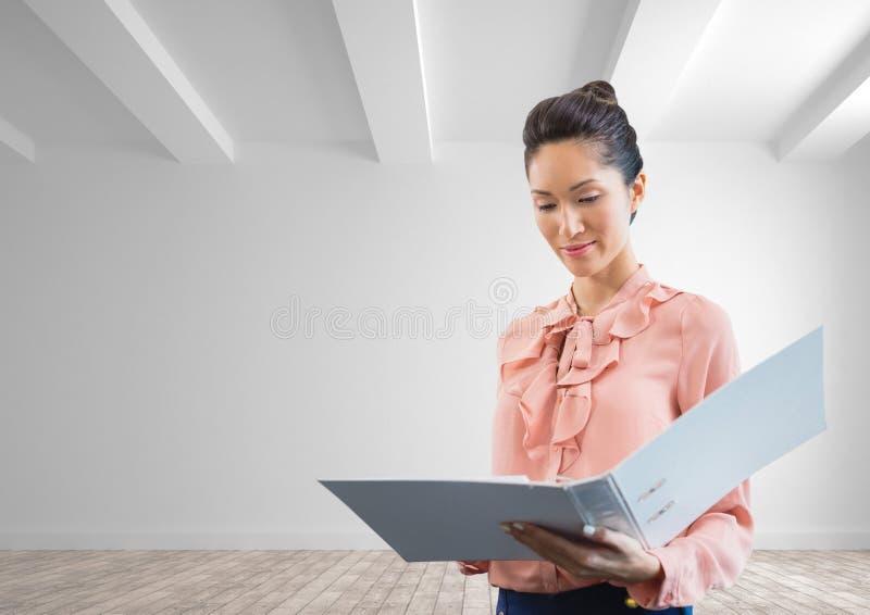 Mujer de negocios que sostiene una carpeta contra el fondo blanco de la pared imágenes de archivo libres de regalías