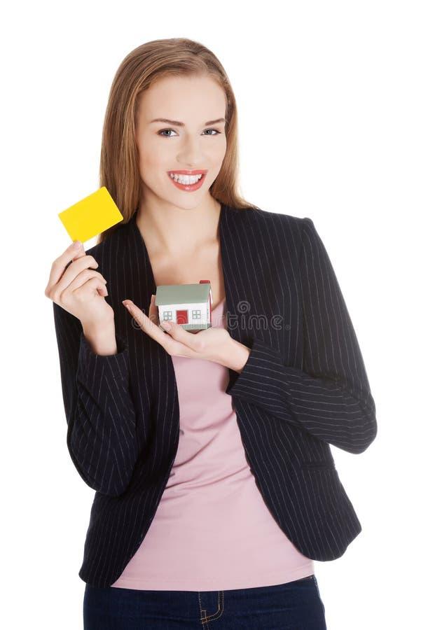 Mujer de negocios que sostiene una casa y una tarjeta fotos de archivo libres de regalías