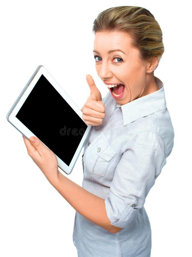Mujer de negocios que sostiene una tableta y que muestra la pantalla y el pulgar negros encima del gesto en el fondo blanco fotos de archivo libres de regalías
