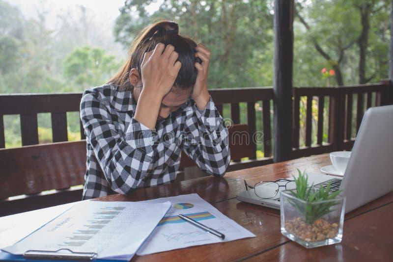 Mujer de negocios que tiene dolor de cabeza mientras que trabaja usando el ordenador port?til Muchacha subrayada y deprimida que  imágenes de archivo libres de regalías