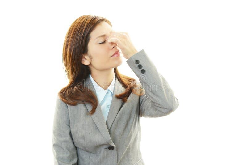 Mujer de negocios que tiene un dolor de cabeza fotografía de archivo
