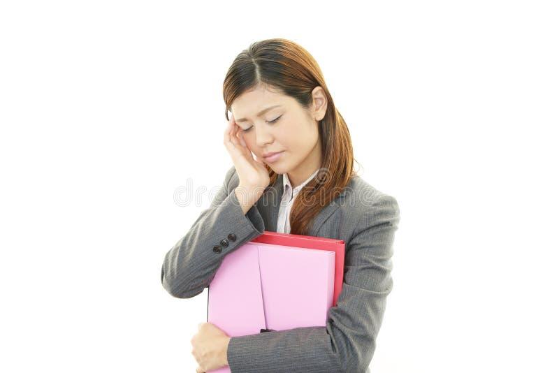 Mujer de negocios que tiene un dolor de cabeza imagen de archivo libre de regalías