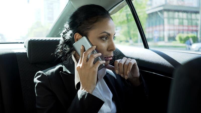 Mujer de negocios que toma en el teléfono en el coche, vida agotadora del jefe de la señora, carrera fotografía de archivo libre de regalías
