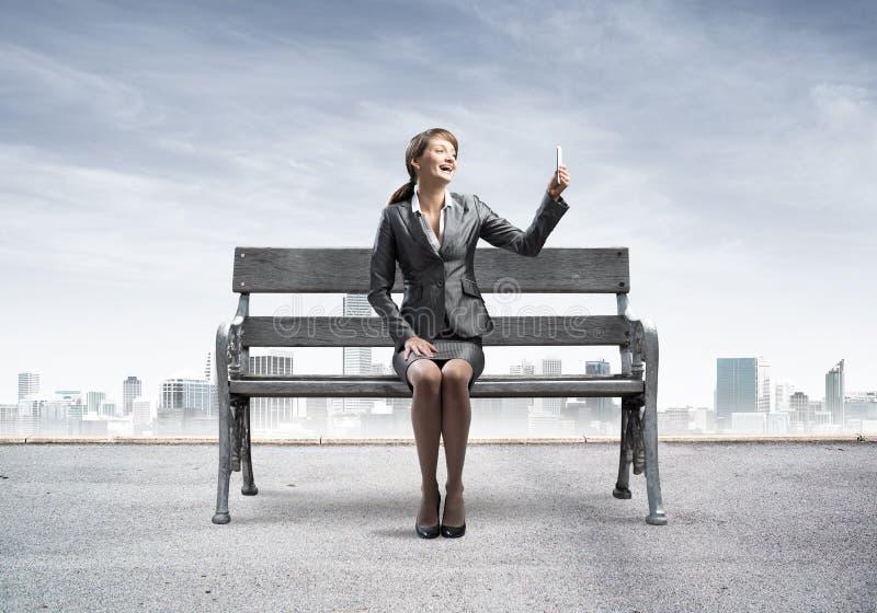 Mujer de negocios que toma la foto o la charla del selfie imagen de archivo libre de regalías