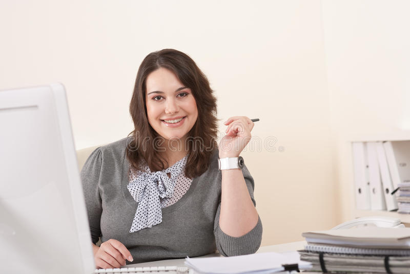Mujer de negocios que trabaja con el ordenador en la oficina fotografía de archivo libre de regalías