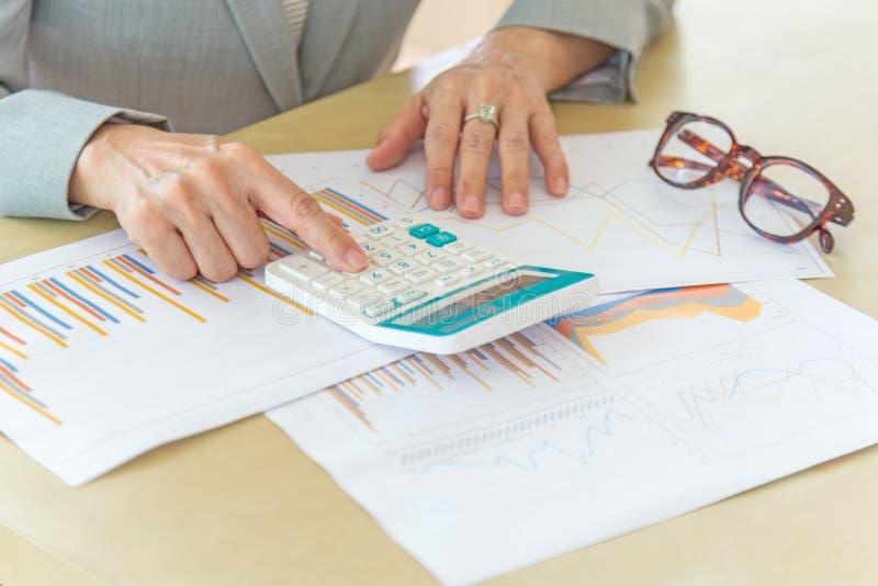Mujer de negocios que trabaja con el ordenador portátil, la calculadora, las lentes y r imagenes de archivo
