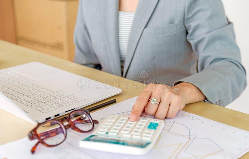 Mujer de negocios que trabaja con el ordenador portátil, la calculadora, las lentes y r fotografía de archivo