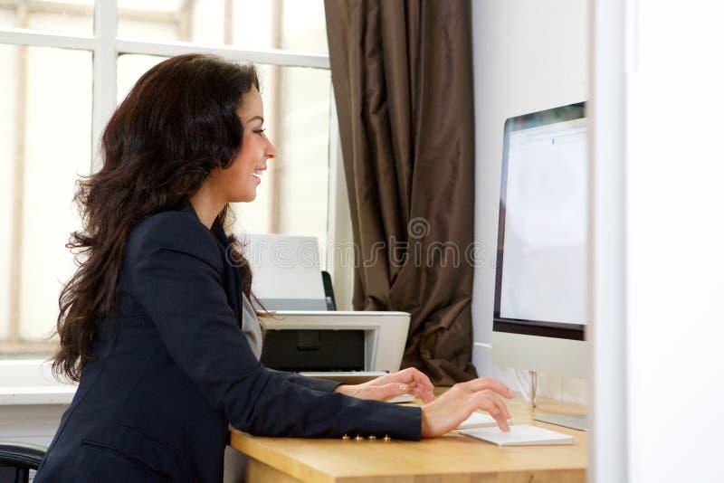 Mujer de negocios que trabaja en el ordenador en oficina imagen de archivo libre de regalías