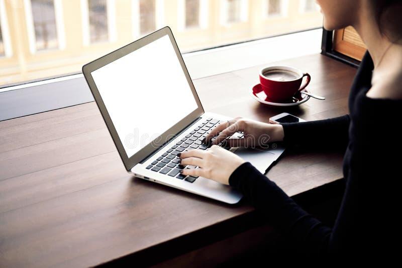 Mujer de negocios que trabaja en el ordenador portátil, capuchino de consumición en cafetería foto de archivo libre de regalías