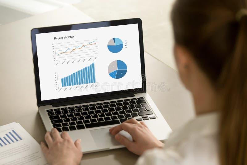 Mujer de negocios que trabaja en el ordenador portátil con estadísticas del proyecto sobre scre fotos de archivo