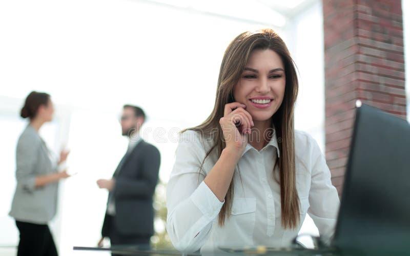 Mujer de negocios que trabaja en el ordenador portátil en oficina foto de archivo