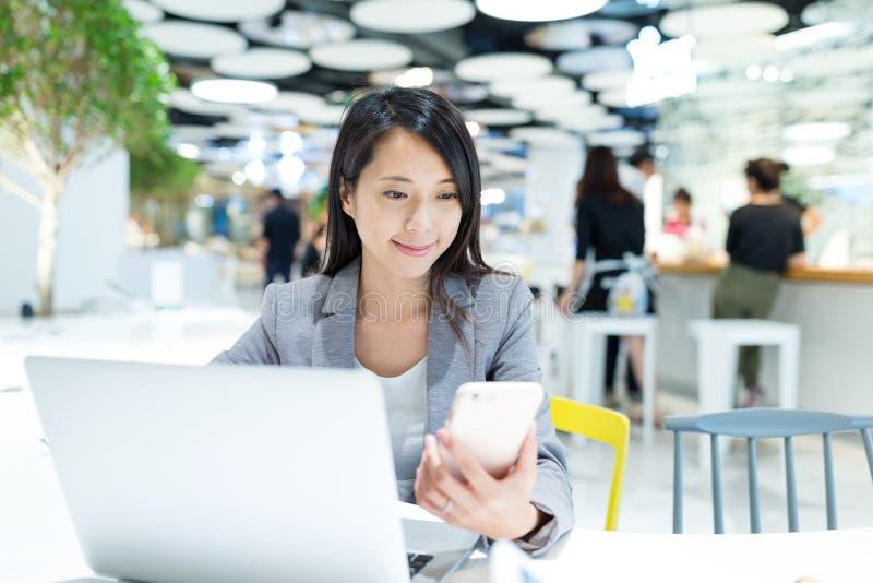 Mujer de negocios que trabaja en el ordenador portátil y el teléfono móvil en offic imagen de archivo