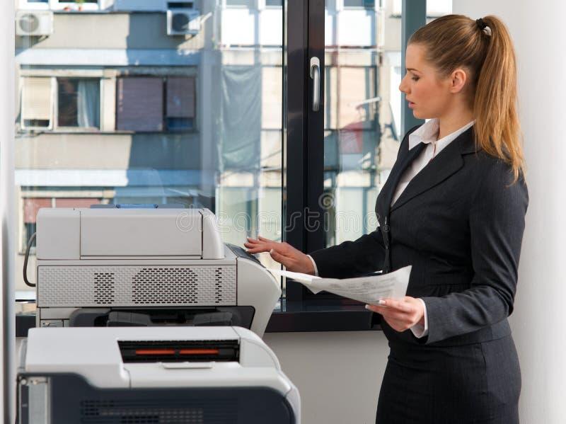 Mujer de negocios que trabaja en la impresora imagen de archivo libre de regalías