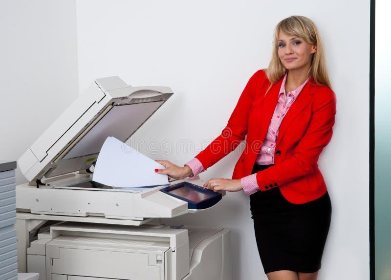 Mujer de negocios que trabaja en la impresora de oficina imagenes de archivo