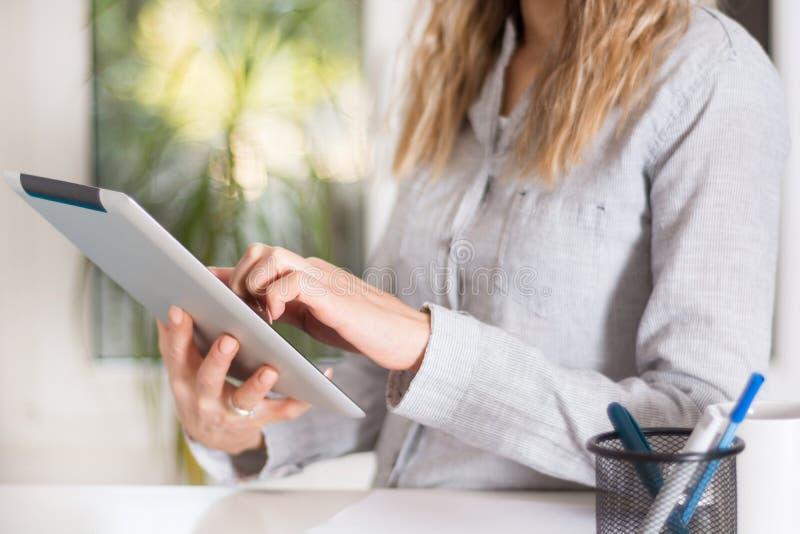 Mujer de negocios que trabaja en la tableta digital en oficina moderna imagen de archivo