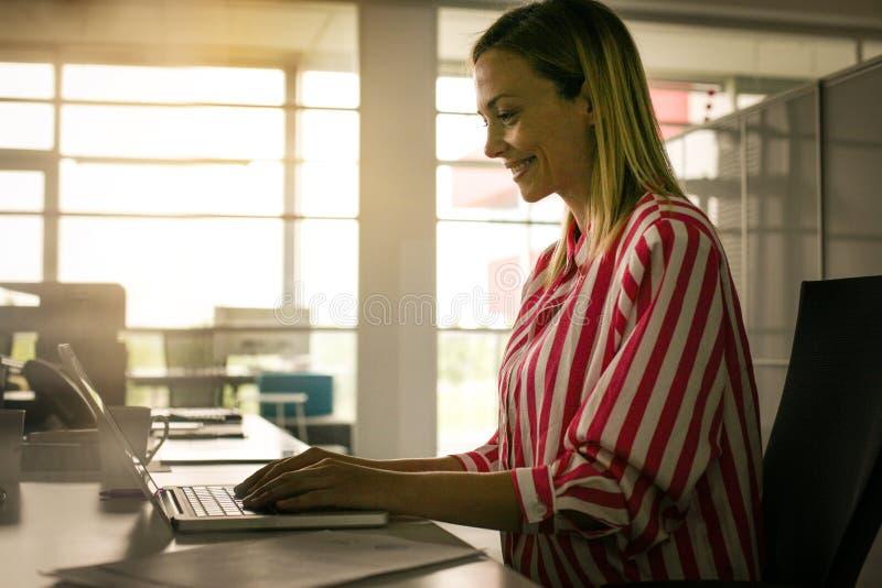 Mujer de negocios que trabaja en oficina Mujer que pulsa en la computadora portátil foto de archivo libre de regalías