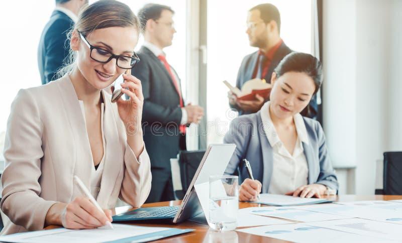 Mujer de negocios que trabaja mientras que los hombres están charlando ocioso fotos de archivo