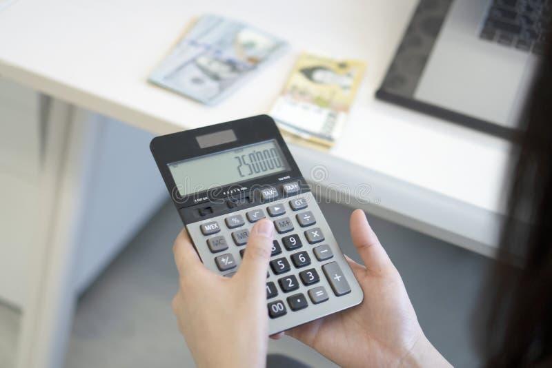 Mujer de negocios que usa la calculadora en oficina foto de archivo