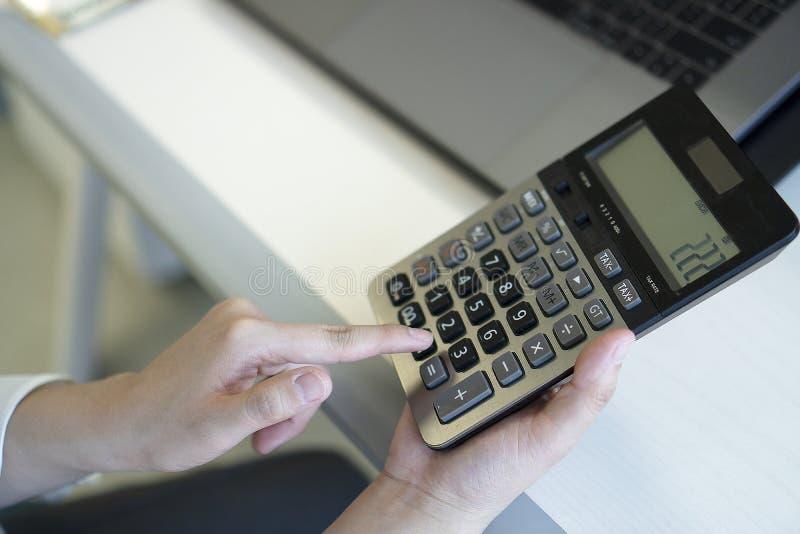 Mujer de negocios que usa la calculadora en oficina foto de archivo libre de regalías