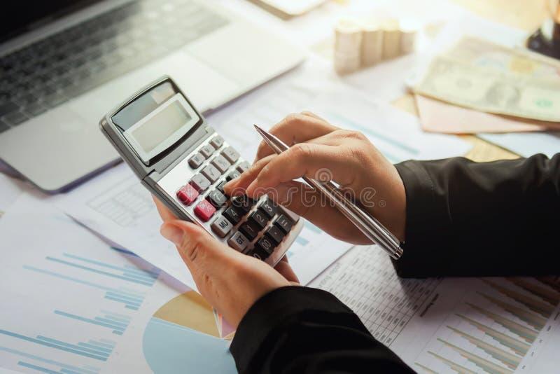 mujer de negocios que usa la calculadora para trabajar en oficina Concepto f foto de archivo libre de regalías