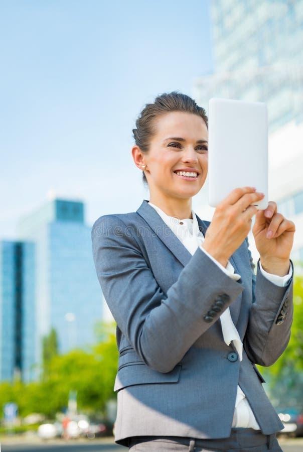 Mujer de negocios que usa la tableta en distrito de oficina moderno imagenes de archivo