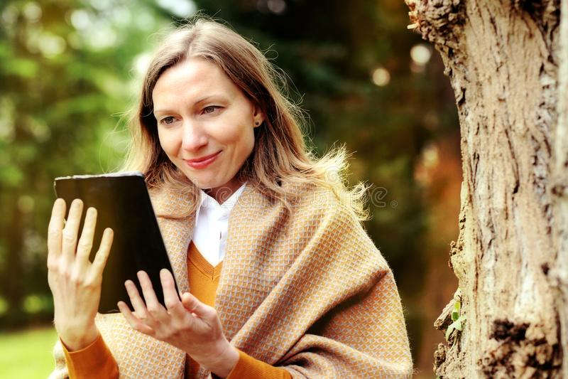 Mujer de negocios que usa la tableta en rotura en otoño foto de archivo