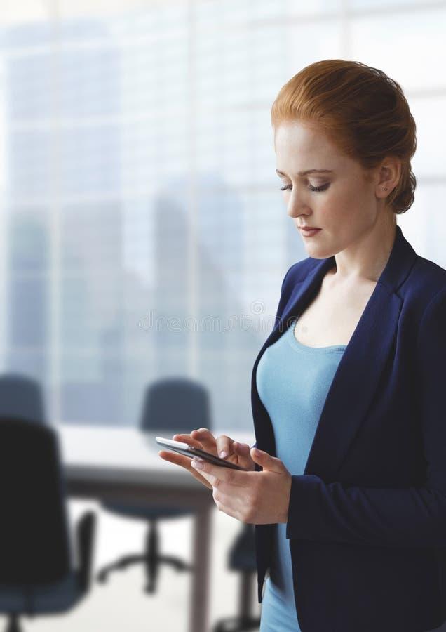 Mujer de negocios que usa un teléfono contra fondo de la oficina imagen de archivo