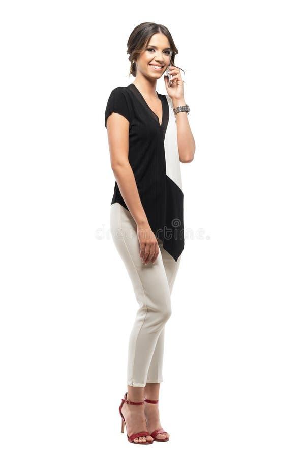 Mujer de negocios relajada feliz joven que habla en el teléfono móvil que sonríe y que mira la cámara fotografía de archivo libre de regalías