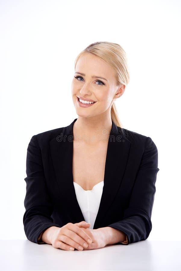 Mujer de negocios rubia adorable que se sienta en el escritorio fotos de archivo