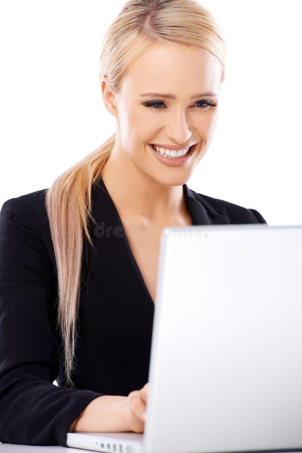 Mujer de negocios rubia adorable que trabaja en el ordenador portátil foto de archivo