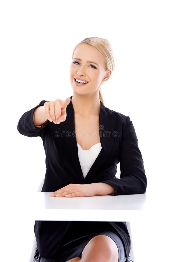 Mujer de negocios rubia atractiva que se sienta delante del escritorio foto de archivo libre de regalías