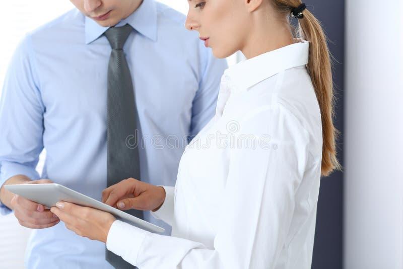 Mujer de negocios rubia hermosa que usa la tableta o la almohadilla táctil con su colega o socio masculino en oficina imagenes de archivo