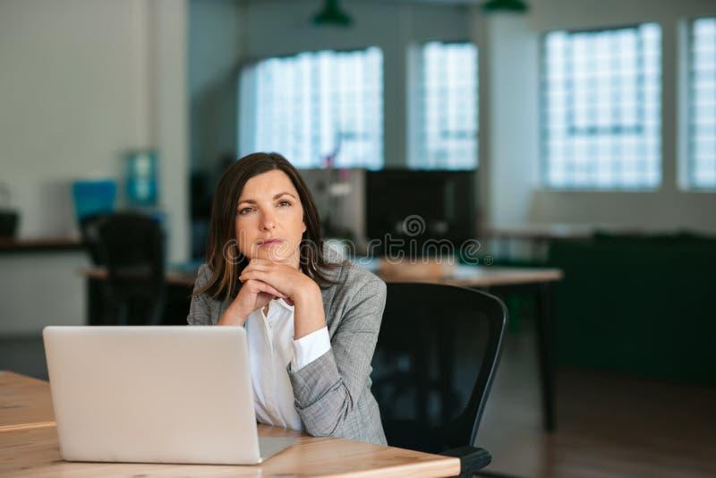 Mujer de negocios sentada en su escritorio pensando en el trabajo fotos de archivo libres de regalías