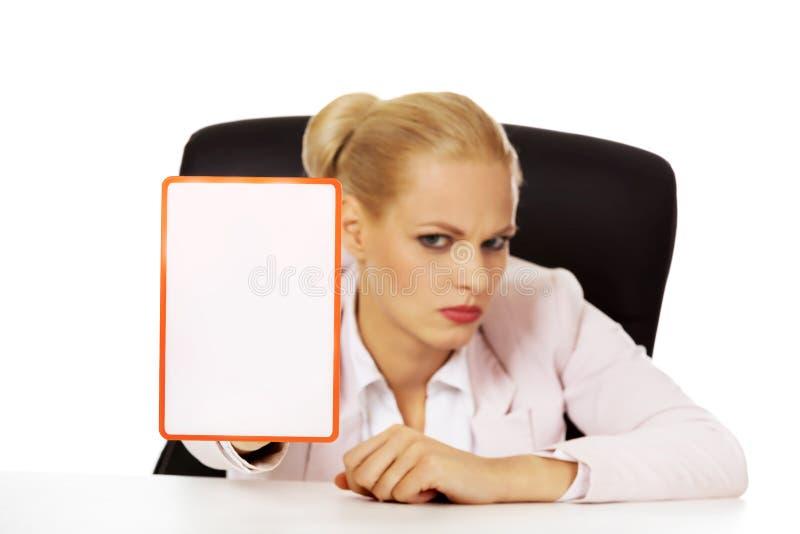 Mujer de negocios seria que se sienta detrás del escritorio y que lleva a cabo al tablero con la prohibición imagenes de archivo