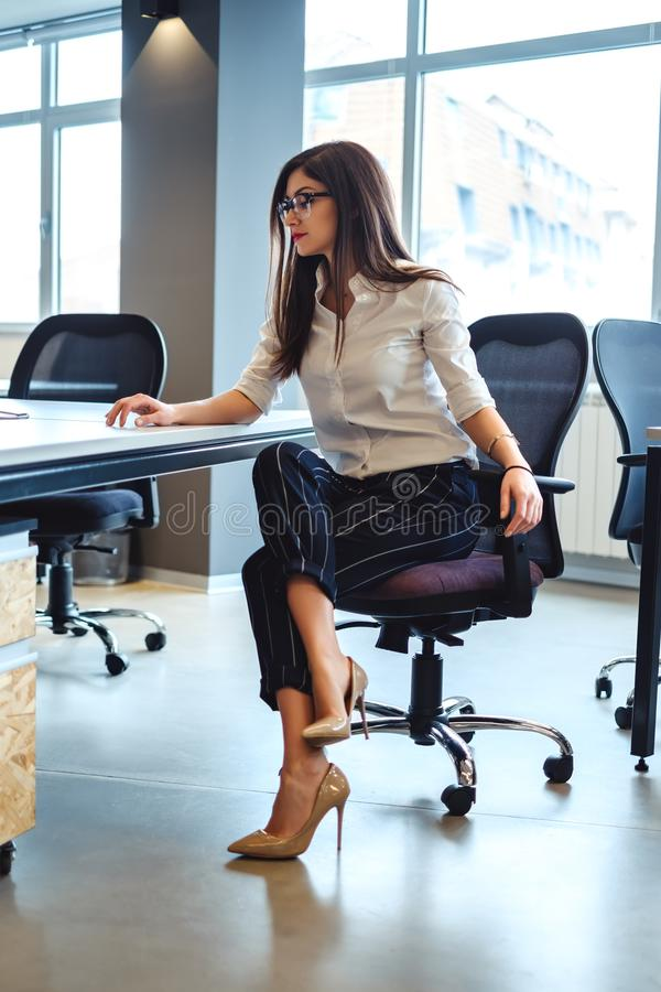 Mujer de negocios seria que sienta y que mira el escritorio imagen de archivo