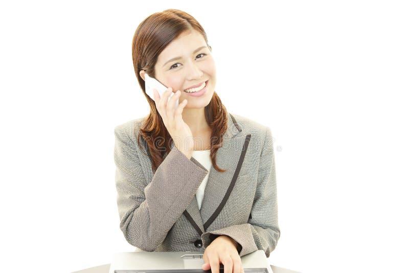 Mujer de negocios sonriente con el teléfono móvil imagenes de archivo