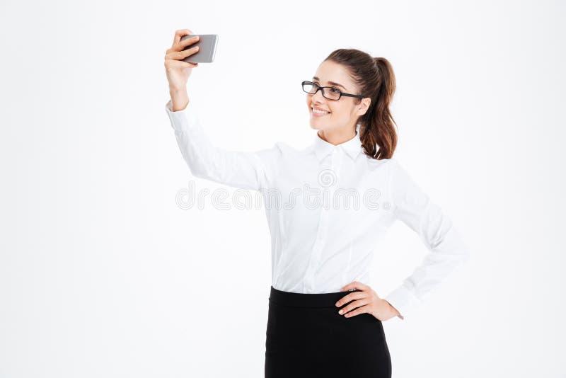 Mujer de negocios sonriente en los vidrios que hacen el selfie usando el teléfono celular foto de archivo